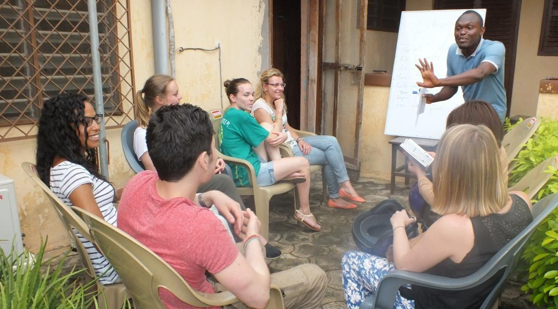 Volunteers listen intently to their dedicated tutor to help them learn a language abroad.